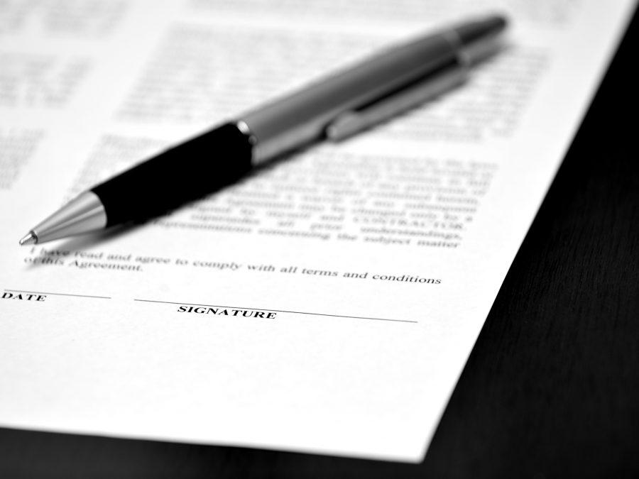 contrato com data e assinatura com caneta em cima