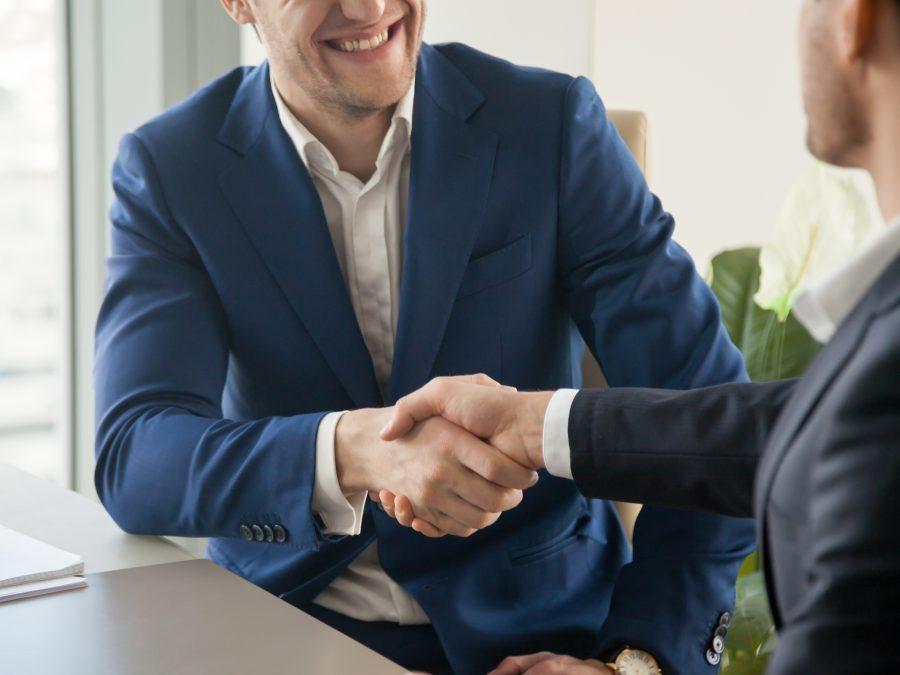dois homens executivos apertando as maos