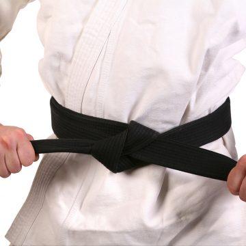 praticante de artes marciais de kimono amarrando a faixa preta